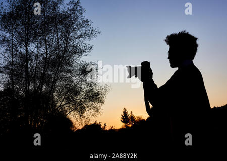 Photographer as silhouette while taking photos at blue hour in nature - Stock Photo