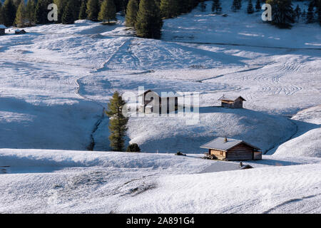 Beautiful view of traditional wooden mountain chalets on scenic Alpe di Siusi with famous Langkofel mountain peaks in the background in golden morning - Stock Photo