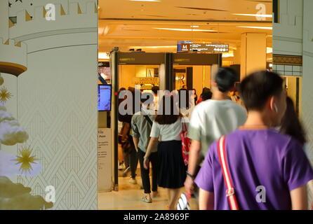 Bangkok, Thailand - November 8 2019 : Blurred motion of people in a row walking through metal detector at entrance of Siam Paragon shopping mall - Stock Photo