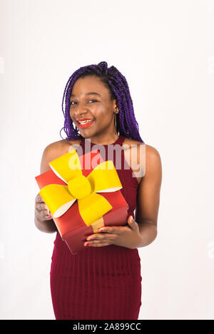 A dark-skinned beautiful model with African pigtails pulls her hands with a gift in her hand. Black cute girl gives a big red gift. The concept of sur - Stock Photo