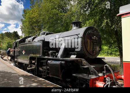 Engineer stepping up to a 1950 black steam engine in Lakeside Station on the Lakeside and Haverthwaite Railway line Cumbria England - Stock Photo