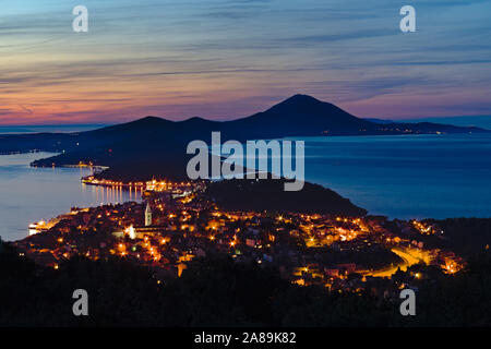 Panoramic view with the sunset light over the town of Mali Losinj, the hills and the Adriatic sea of this beautiful archipelago of Croatia - Stock Photo