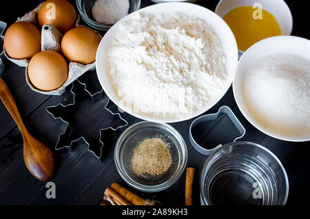 Set of ingredients for cooking festive Christmas gingerbread cookies - butter, flour, sugar, eggs, spices with  sugar decor, icing, forms for biscuits - Stock Photo