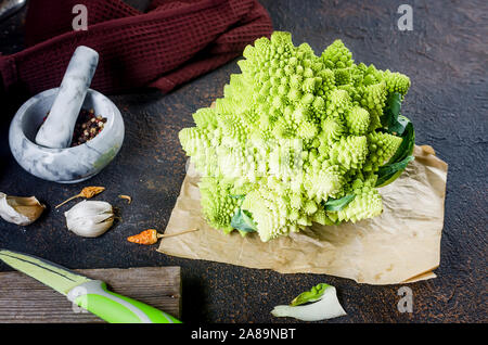 Fresh green romanesco, Raw Organic Cabbage Ready for Cooking on a cutting board on dark wooden background - Stock Photo