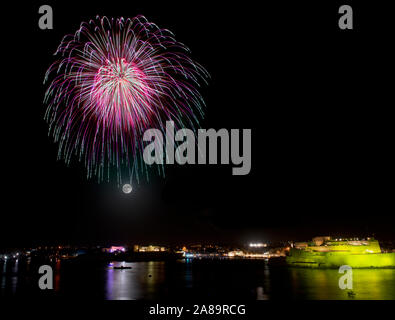 fireworks explosion in dark sky with city silhouette and colorful reflect on water - Stock Photo