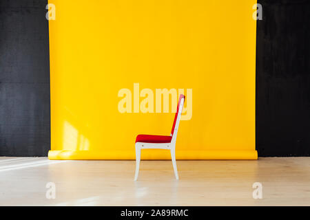 one red chair in the interior of the room with a yellow background