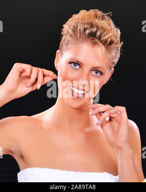 Junge blonde Frau pflegt und reinigt ihre Zähne mit Zahnseide, MR: Yes - Stock Photo
