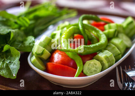 Fresh vegetables - green peppers, tomatoes, cucumbers and greens on table. Traditional turkish breakfast. - Stock Photo