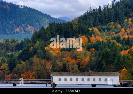 Autumn colors in the Cascade Mountain Range, where a covered bridge sits along the shore of a lake Stock Photo