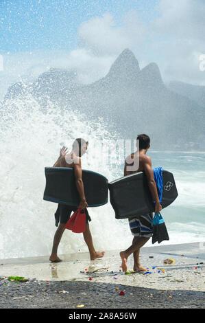 RIO DE JANEIRO - MARCH 16, 2011: Young Brazilian surfers walk on the Ipanema boardwalk carrying bodyboards and fins near crashing waves at Arpoador.