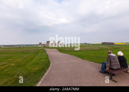 Old couple seated looking Stonehenge,  a ring of standing stones, prehistoric monument, Wiltshire, England, UK - Stock Photo