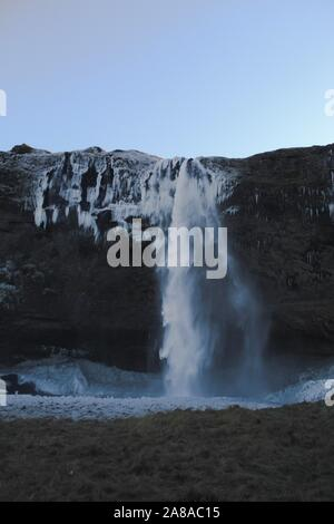The Seljalandsfoss waterfall in Southern Iceland on a clear day with blue skies. - Stock Photo