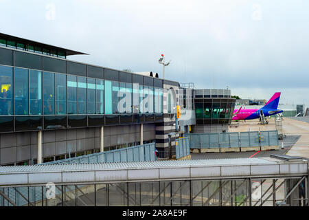 Terminal glass facade, airplane at runway by Dortmund international airport, cloudy skyline, Dortmund, Germany - Stock Photo
