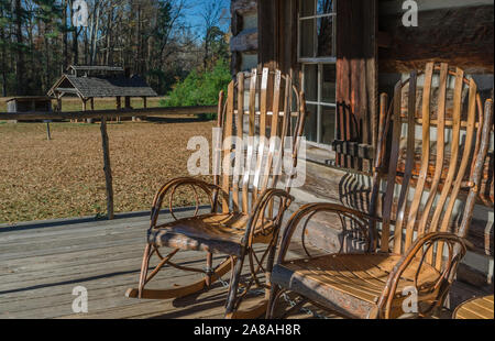 Amish-made rockers sit on the porch of the Log Cabin Gift Shop in French Camp, Mississippi. - Stock Photo
