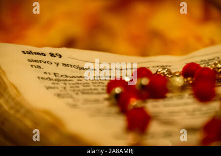 Old Spanish Bible book is open at Psalms Salmo, with rosary beads laying on top. - Stock Photo