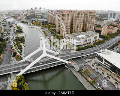 Aerial view cityscape of Tianjin ferris wheel. Famous Tianjin Eye ferris wheel above the Yongle Bridge and the Haihe river. Popular modern landmark in Tianjin, China. October, 28th, 2019 - Stock Photo