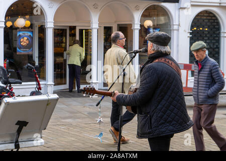 a middle aged busker signing at a microphone while playing the guitar with shoppers passing by - Stock Photo