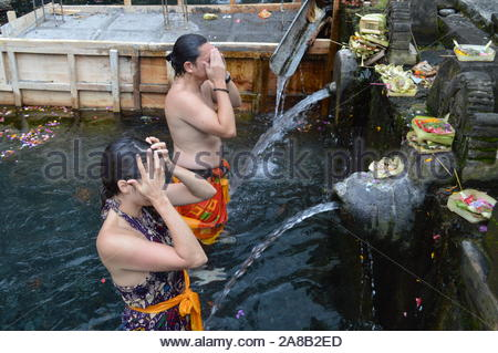 Man and woman taking a bath standing in body of water with fountains - Stock Photo