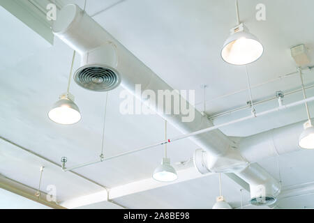 Air duct, air conditioner pipe and fire sprinkler system on white ceiling wall. Air flow and ventilation system. Building interior. Ceiling lamp light - Stock Photo