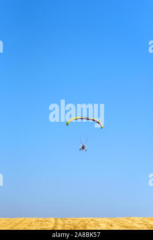 Powered paraglider parachute against blue sky and yellow field. Paramotor flying in sunny day. Freedom and summer holiday concept, extreme sport. - Stock Photo
