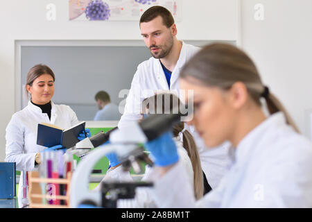 Group of young Laboratory scientists working at lab with test tubes and microscope, test or research in clinical laboratory.Science, chemistry, biolog - Stock Photo