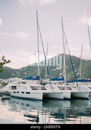 Charter catamaran sailboats waiting in the Road Town harbor on Tortola island, British Virgin Islands
