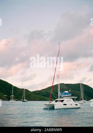 White catamaran sailboat at sunset in the harbor at the Bitter End Yacht Club, Virgin Gorda, British Virgin Islands, Caribbean