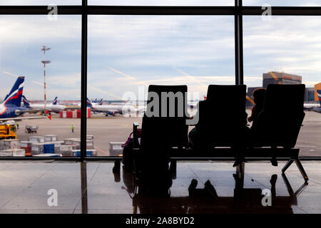Russia Moscow 2019-06-18 airport waiting hall, lounge with seats overlooking the runway and airplanes, people, passengers, tourists silhouette against - Stock Photo