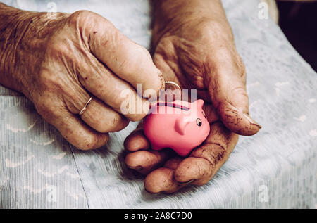 Close up view of old dirty rough elderly retired woman hands holding tiny pink piggy bank. Small pension concept.