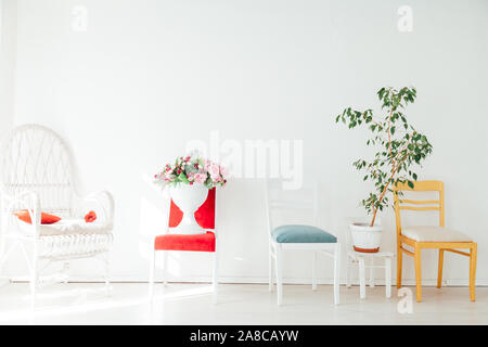 different chairs with flowers and plants in the white room - Stock Photo