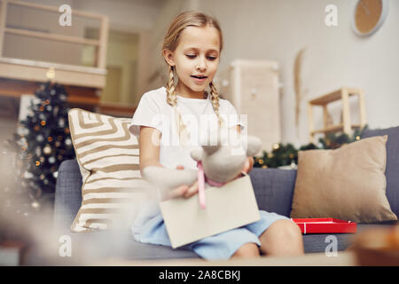 Happy little girl with blond hair looking at teddy bear in her hands while she opening the Christmas present on the sofa at home - Stock Photo