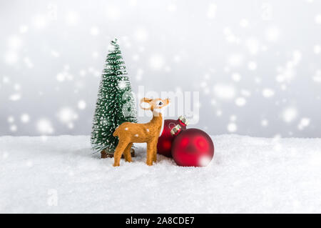 Miniature reindeer standing near fir tree and red Christmas ornaments under falling snow. Christmas holiday theme against light festive background wit - Stock Photo