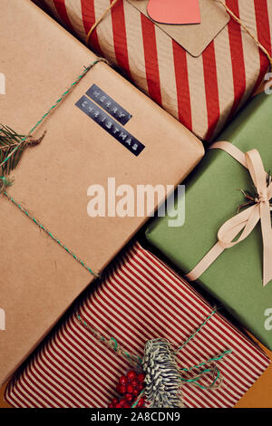 Close-up of decorated gift boxes wrapped in colorful wrapping paper made for Christmas - Stock Photo