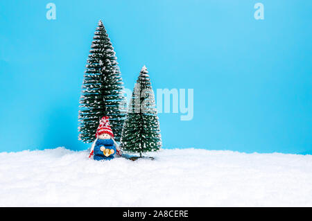 Cute small toy child in blue knitted sweater holding bell. Cute Christmas figure as a handmade holiday decoration against blue background with copy-sp - Stock Photo
