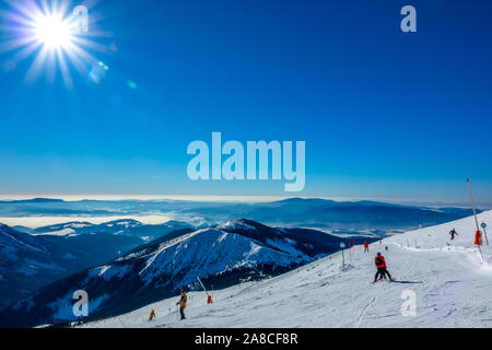 Winter Slovakia. Ski resort Jasna. Panoramic view from the top of the snow-capped mountains and ski slope with skiers - Stock Photo