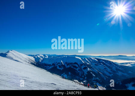 Winter Slovakia. Ski resort Jasna. View from the top of the snow-capped mountains and ski slope with skiers - Stock Photo