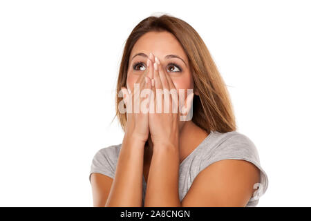 happy young woman covers her face with her hands