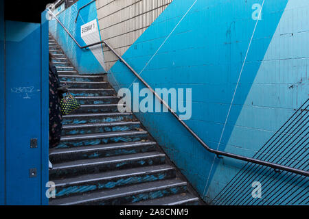 Londoners pass down the underpass steps leading into the Old Street station in Shoreditch, on 5th November 2019, in London, England. - Stock Photo