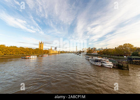 River Thames looking towards Westminster Bridge with Palace of Westminster, Houses of Parliament, and river boats moored up near Lambeth Bridge - Stock Photo