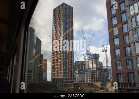 Trackside apartments and flats at the Nine Elms regeneration development in Battersea, seen through the window of a Southern train carriage window, on 7th November 2019, in London, England - Stock Photo