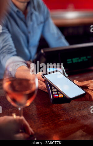Close Up Of Woman Paying For Drinks At Bar Using Contactless App On Mobile Phone - Stock Photo