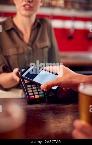 Close Up Of Man Paying For Drinks At Bar Using Contactless App On Mobile Phone - Stock Photo