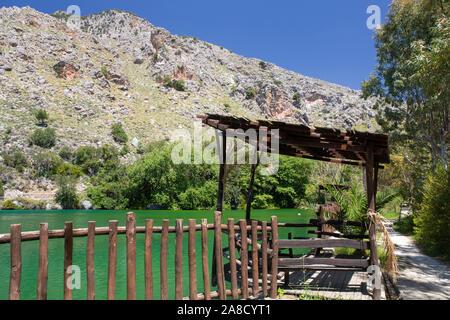 Zaros, Heraklion, Crete, Greece. Wooden shelter beside the emerald waters of Lake Votomos. - Stock Photo