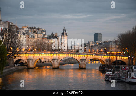 Pont Neuf in Paris. One of the most famous bridge in europe in a beautiful night with all the lights on. And an amazing river, the seine. - Stock Photo