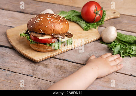 girls hand near onion and tomatoes, wooden table - Stock Photo
