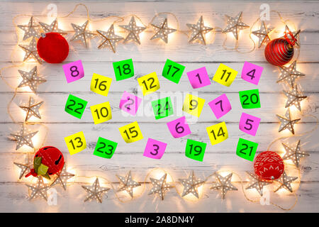 Advent calander parer notes, with a border of golden star christmas lights and red baubles, on a distressed white wooden board - Stock Photo