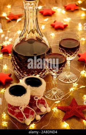 A decanter of port and crystal glasses with christmas lights, baubles and red stars decorations, on a wooden table - Stock Photo