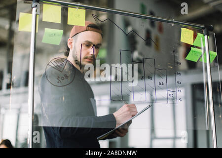 Young man in casual outfit and cap working with datas and diagrams on glass office wall with sticky notes, while his coworkers discussing ideas and - Stock Photo
