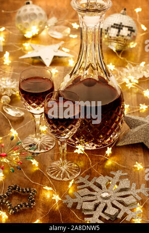 A decanter of port and crystal glasses with christmas lights, baubles and silver stars decorations, on a wooden table - Stock Photo