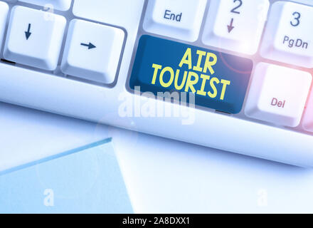 Handwriting text Air Tourist. Conceptual photo process of going from place to place by any flying object White pc keyboard with empty note paper above - Stock Photo